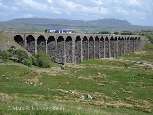 A class 158 train crossing Ribblehead Viaduct, with Pen-y-ghent beyond.