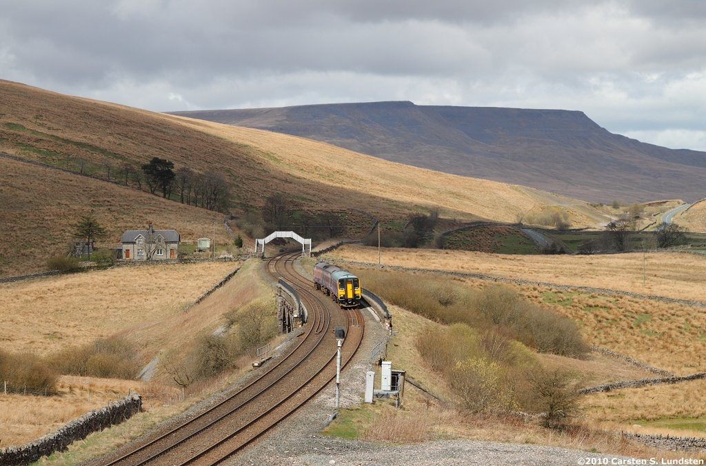 Photograph: Train with Grisedale footbridge and Wild Boar Fell beyond.